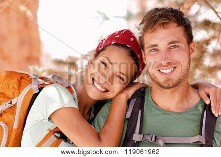 Happy young hikers backpacking on summer travel. Portrait of two friends teenagers or student couple wearing rucksacks bags smiling hiking during road trip vacation or doing volunteering. poster