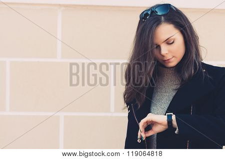 Beautiful Young Woman In A Black Coat Checks The Time On The Clock On The Background Of Beige Wall