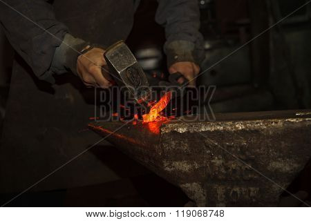 A blacksmith forging hot iron on the anvil poster