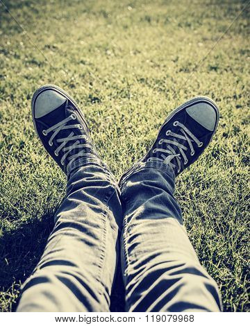 Closeup photo of lazy teen guy lying down on green grass an wearing stylish trendy gumshoes, body part, relaxing outdoors, sportive shoes, fashion for hipster