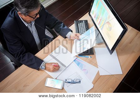 Senior Business Man Looking To Business Paper Graph Report In Hand And Writing Strategy Analysis Pla