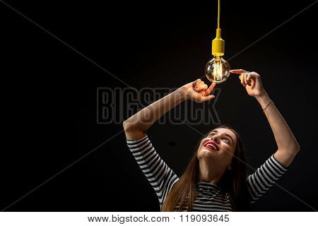 Young female inventor with illuminated lamp
