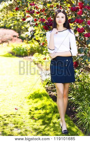 Young Beautiful Tall Woman With Long Straight Dark Hair Posing At Spring Garden