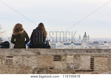 BUDAPEST, HUNGARY - FEBRUARY 02: Two girls sitting on wall enjoying the view from Buda Castle, with Gresham Palace and Saint Stephen's Basilica in the background. February 02, 2016 in Budapest.