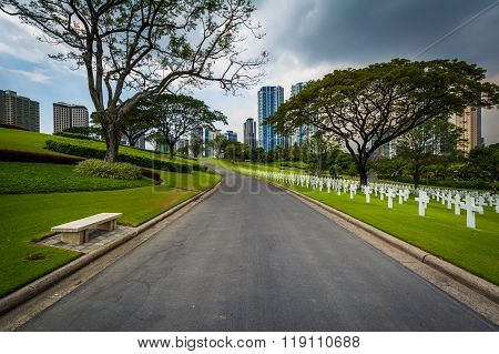Road And Graves With Modern Buildings In The Distance At The Manila American Cemetery & Memorial, In