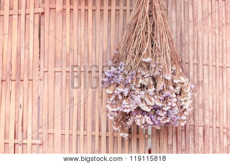 Bouquet Of Dried Flowers Hanging On Bamboo Background