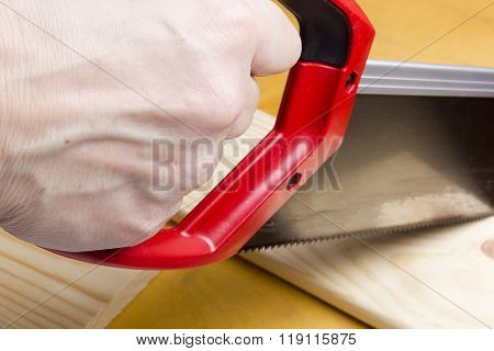Close Up Of Builders With Arm Saw Sawing Board