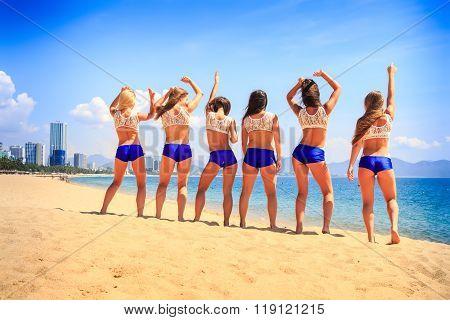 Cheerleaders Stand Backside View On Beach Against Azure Sea