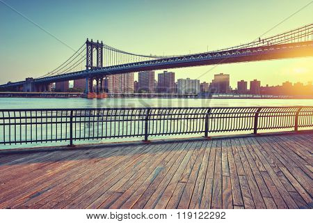 View of Manhattan Suspension Bridge Spanning the East River at Sunset with View of Manhattan from Boardwalk in Waterfront Brooklyn Park, New York City, New York, USA