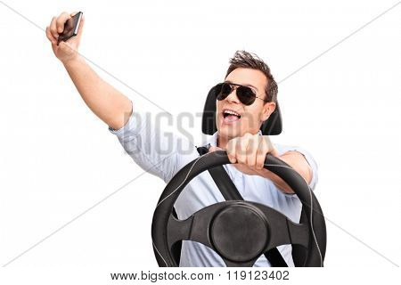 Young man driving and taking a selfie with his cell phone isolated on white background