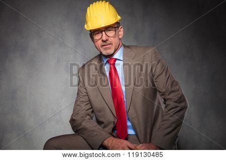 portrait of elegant senior engineer wearing glasses and helmet while posing seated in studio background