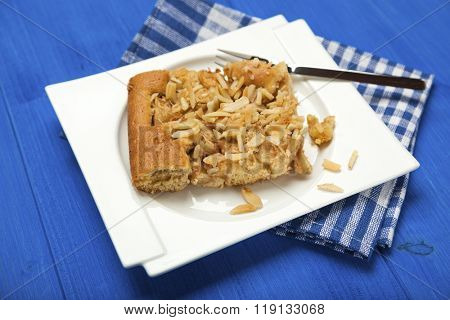 piece of homemade apple cake with almond slivers on plate with fork on blue wooden table