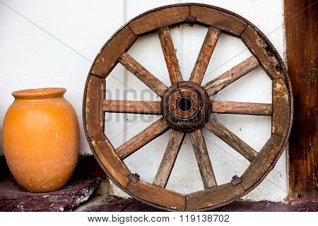 old wooden wheel and jug clay on white wall background