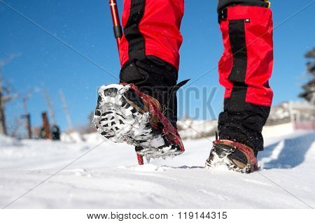 View Of Walking On Snow With Snow Shoes And Shoe Spikes In Winter.