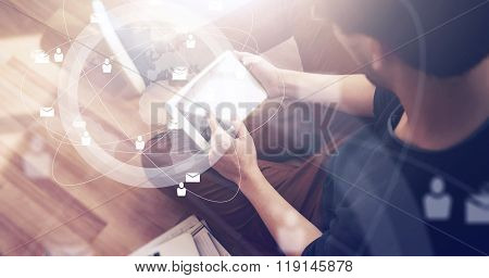 Photo of businessman touching screen Of generic design tablet holding in his hands. Laptop on the fl