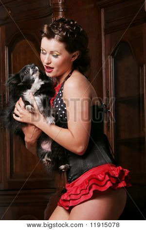 Gorgeous young pinup style woman playing with her puppy poster