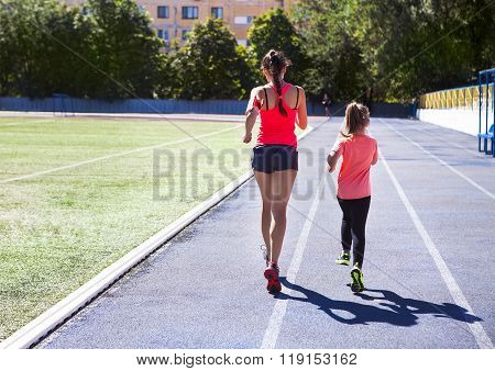 Mother And Little Daughter Are Doing Exercise In The Stadium. Healthy Family Concept