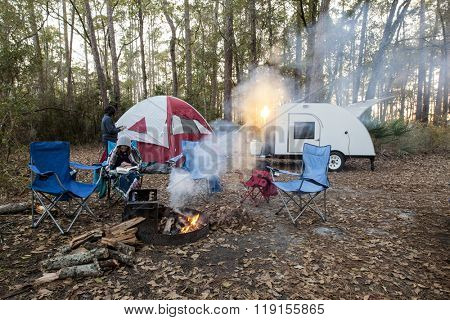 Family camping with tent and teardrop trailer at sunset with light coming through smoke