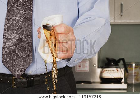 Businessman crushing coffee cup