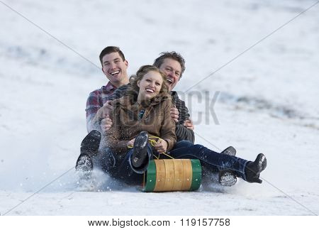 Happy adult family enjoying some winter fun on a toboggan.