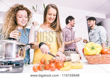 Group Of Friends Cooking At Home To Have Dinner Together