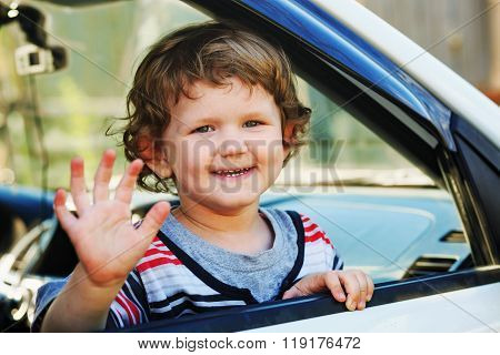 Little Boy Leaned Out The Window Of A Car And Waving His Hand.