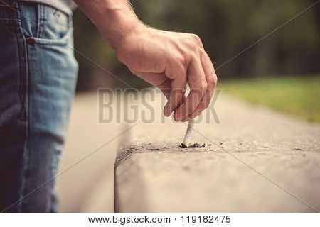 Hand of a young man extinguish cigarette