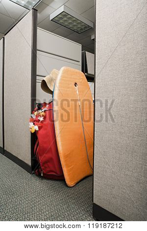 Suitcase and body board in office cubicle