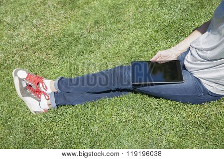 Sitting On Grass With Tablet