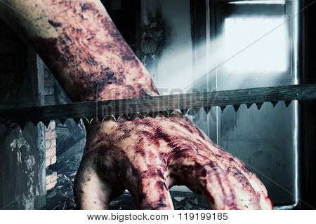 Cutting Into Bloody Hand With Saw Blade In Front Of Lighten Door And Grunge House
