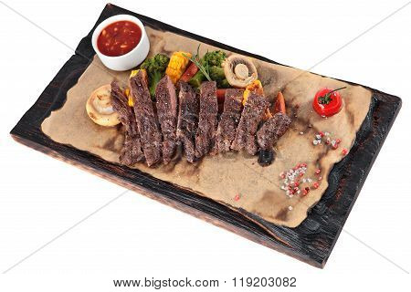 Sliced Grilled Skirt Steak with vegetables on a dark wooden board isolated on white background. poster