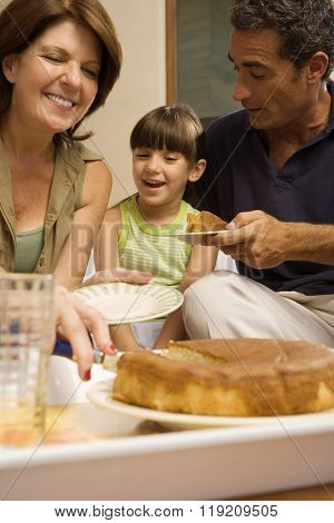Girl having cake with grandparents