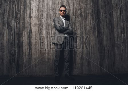 Handome Rigid Man With Glasses In Suit On The Grey Background Crossing Hands