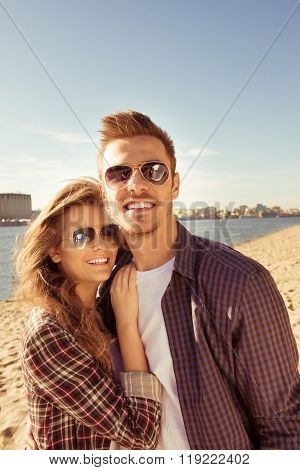 Smiling Couple In Love In Spectacles  Hugging On The Seaside