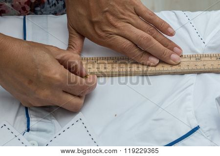 A hand of marking a uniform , Marking, A tailor is laying out a dress/Sewing layout