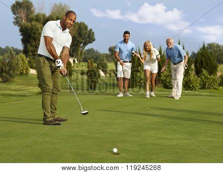 Male golfer putting in golf ball on the green, partners jittering.
