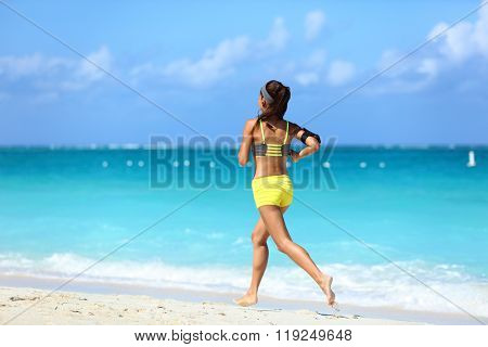Running on beach - summer workout active lifestyle. Female athlete from the back running away barefoot on the sand in trendy activewear outfit training cardio for weight loss.
