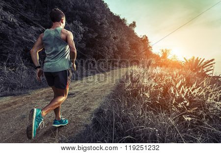 Man jogging on the gravel road at sunset
