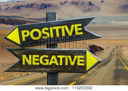Positive - Negative signpost in a desert road on background