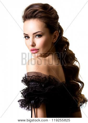 Beautiful face of an young sexy woman in black dress posing at studio on white background