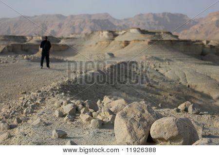 Pilgrim in the Judea Desert. Salt and rocks at Dead Sea, Israel