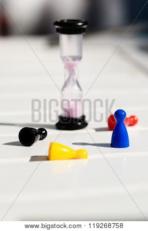 Multi-colored chips and hourglass on a white wooden table. The three chips knocked down on the table