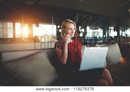 Young businesswoman talking on mobile phone while sitting with open net-book on knees in cozy cafe