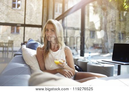 Charming young female with glass of cocktail resting after work on net-book while sitting in bar