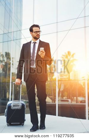 Serious male CEO waiting for a call on cell telephone before his business trip