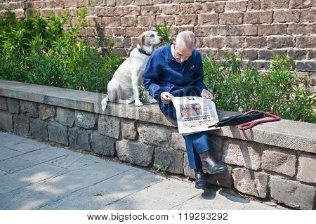 The Man Reading A Newspaper With His Dog