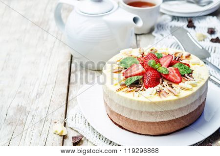 Three Chocolate Cake Decorated With Strawberries And Mint Leaves