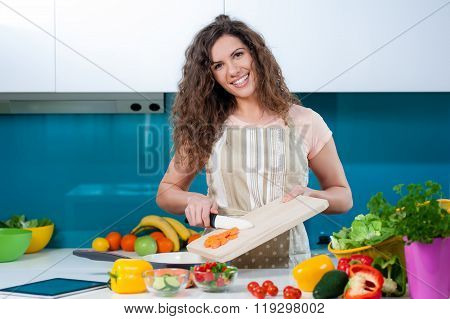 Woman cutting a carrot and playing with knife.