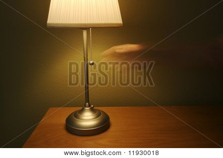 Abstract of modern lamp against green wall on wood table. Ghosted hand reaches for light switch.