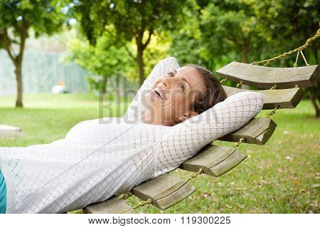 Smiling Older Woman Relaxing On Hammock Outdoors